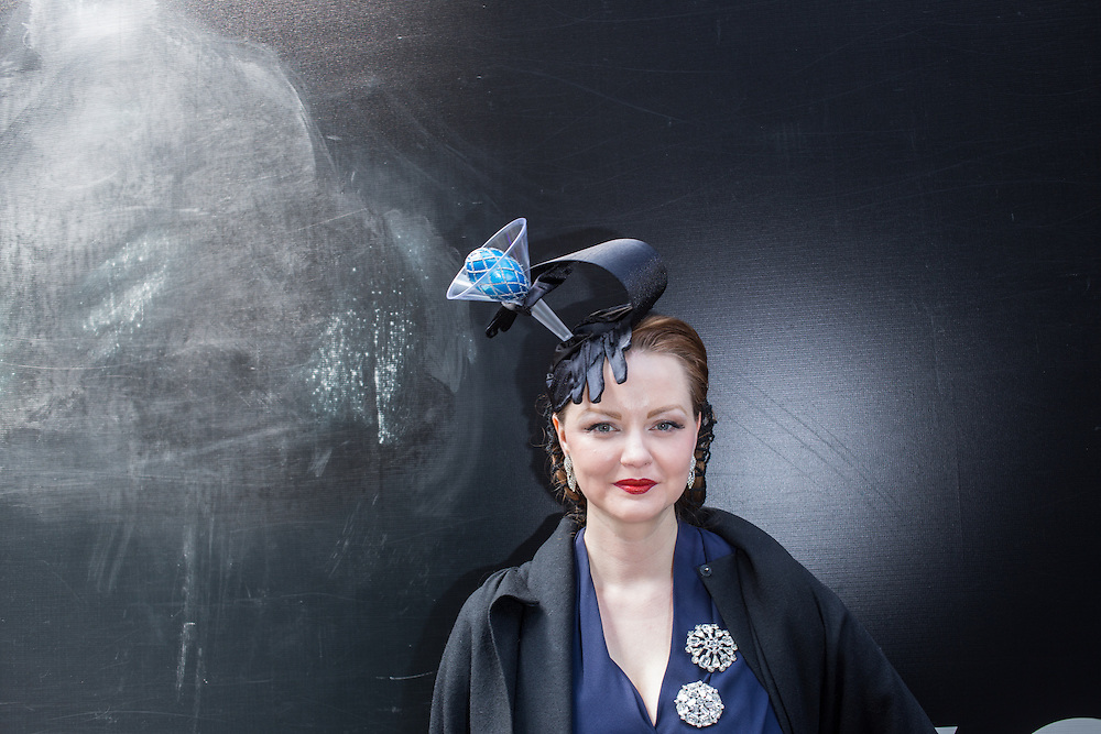 New York, NY, USA-27 March 2016. A woman wears a retro-themed hat with a black-gloved hand holding a martini glass with a blue egg in it  in the annual Easter Bonnet Parade and Festival.