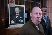 A smoking cigar aficionado inhales in front of a portrait of Winston Churchill, outside Sautter Cigars, on 20th January 2017, in Mount Streeet, Mayfair, London, England.