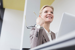 Businesswoman in office with laptop, smiling