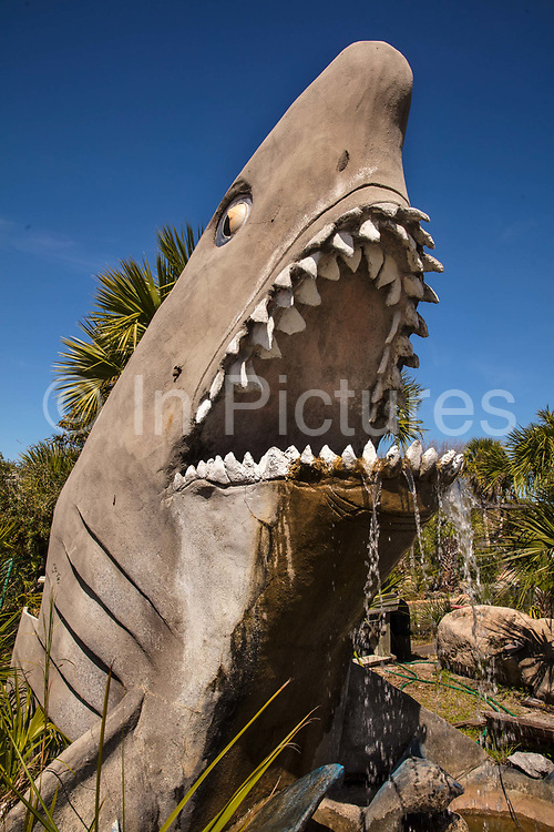 Old concrete shark waterfall in Pirate's Island Adventure Golf on 6th March 2020 in Panama City, Florida, United States. With an average of 320 days of Florida sunshine each year – and 27 miles of sugar-white sands bordering the clear, emerald green waters where the Gulf of Mexico and St. Andrew Bay converge – Panama City Beach is a favourite of travellers seeking an affordable beach vacation with year round offerings.