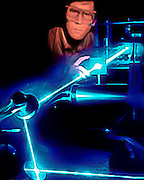 A lab technicial tests a laser beam.