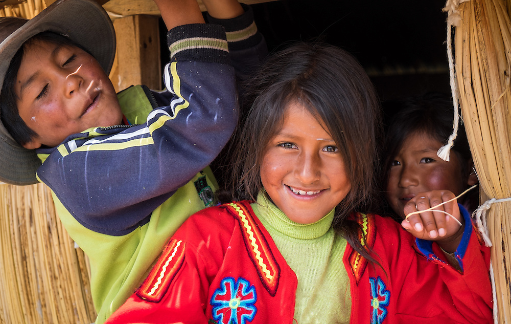 UROS ISLANDS, PERU - CIRCA APRIL 2014: Kids brothers from Uros Islands in Lake Titicaca, in from of their traditional hut.