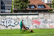 A worker mows the lawn along a section of the Berlin Wall, at the memorial for the victims of the Berlin Wall on Bernauer street in Berlin, Germany, August 12, 2021. The order for the start of the construction of the Berlin wall was issued on 13 August, 1961. The barrier which consists of roughly 43 kilometer of concrete wall, watch towers, check-points, barbed wire and mines, creating a border strip separating the former Western Allies' enclave of West Berlin, from the rest of the city under DDR control. The wall stood until the 9th of November, 1989.