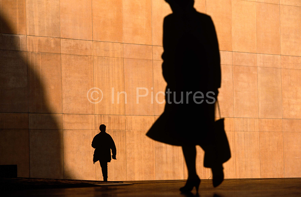 We see two office workers silhouetted against the large orange wall  of the Credit Lyonnais Bank, rushing to work through Broadgate in the City of London, UK. The figures are reduced to black shapes and without detail that may identify them or their clothes, are hurrying in different directions, one is a lady carrying a bag  but the feeling of rushing business is seen and their scale is ambiguous because  we don't know how close or far away they are from each other. The female therefore looks a  giant and the man, tiny. Broadgate Estate is a large, 32 acre (129,000 m²) office and retail estate in the City of London, owned by British Land and managed by Broadgate Estates. It was originally built by Rosehaugh and was the largest office development in London until the arrival of Canary Wharf in the early 1990s.