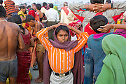 A boy is standing, hands on his head, among a crowd of Hindu devotees near a bathing ghat (riverside) on the holy Ganges River during the yearly Sonepur Mela, Asia's largest cattle market, in Bihar, India.