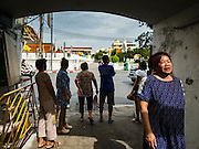 15 AUGUST 2016 - BANGKOK, THAILAND: A resident of the Pom Mahakan slum walks away from the entrance to the slum just before Bangkok city officials arrived to serve eviction notices. Final eviction notices were posted today and residents of the slum have been told they must leave the fort by September 3, 2016. The Pom Mahakan community is known for fireworks, fighting cocks and bird cages. Mahakan Fort was built in 1783 during the reign of Siamese King Rama I. It was one of 14 fortresses designed to protect Bangkok from foreign invaders. Only two of the forts are still standing, the others have been torn down. A community developed in the fort when people started building houses and moving into it during the reign of King Rama V (1868-1910). The land was expropriated by Bangkok city government in 1992, but the people living in the fort refused to move. In 2004 courts ruled against the residents and said the city could take the land.      PHOTO BY JACK KURTZ
