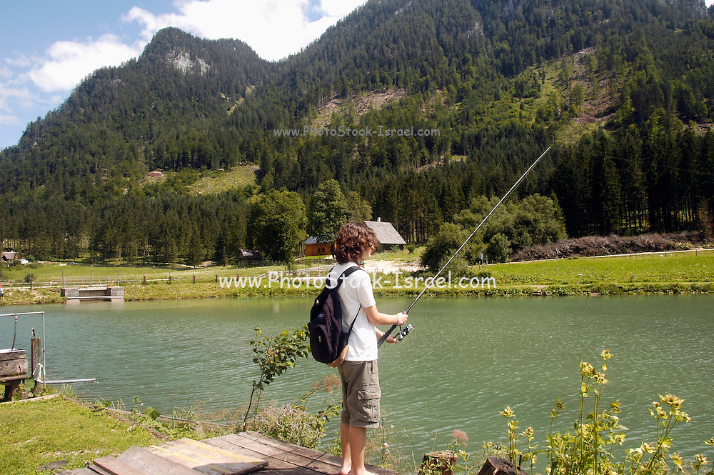 Austria, Upper Austria, Gosau, in the Dachstein Mountains. Teen boy fishing in the lake. Model release available