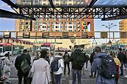Nederland, Nijmegen, 8-11-2018 Bij het busstation van de stad staan mensen te wachten om in te stappen in de bus. Het is stadsvervoer in een stadsbus van vervoerder Breng die ook regionaal vervoer verzorgt . Op de achtergrond een flat van studentenhuisvesting, studentenflat, met op de begane grond poppodium Doornroosje.Foto: Flip Franssen