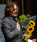 American actor Johnny Depp carrying a bouquet of flowers given by his supporters greets and smiles at his supporters and the members of the press as he arrives at the High Court in London on Thursday, July 23, 2020 - to attend the hearing of his legal dispute with UK tabloid newspaper The Sun over allegations he assaulted his former wife Amber Heard. (VXP Photo/ Vudi Xhymshiti)
