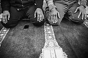 Men sit on the floor to pray at ISBCC in Boston, Massachusetts, 2010.