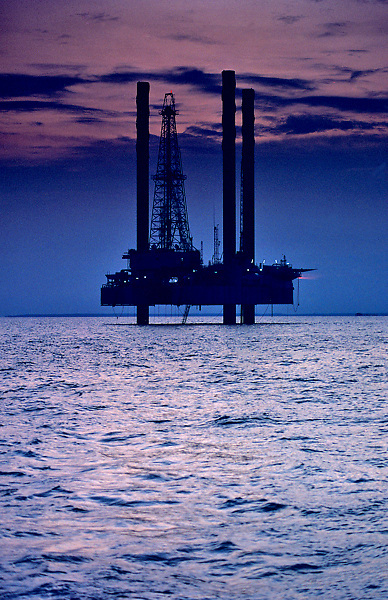 Silhouetted jackup offshore oil drilling rig with a purple sunset reflecting in the water.