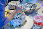 Decorating a birthday cake with icing sugar unicorn