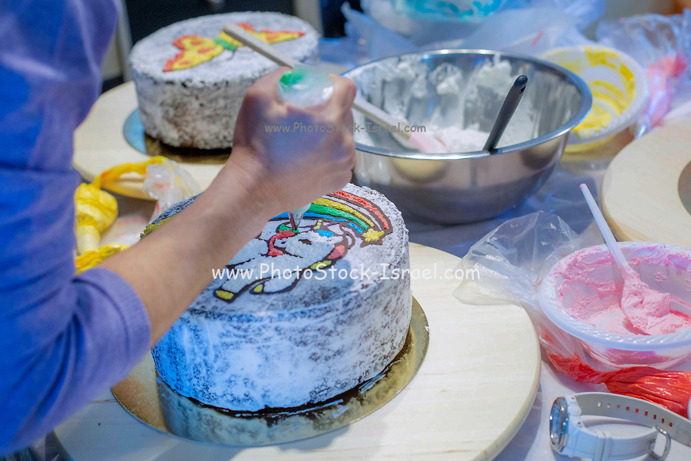 Decorating a birthday cake with icing sugar unicorn