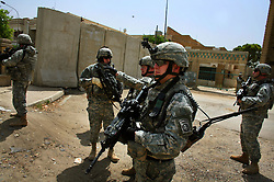Surrounded by a security detail, Lt. Col. Wilson Shoffner (center-left), commander of 2-319 2BCT 82nd Airborne Division, is given a tour of portions of a wall (in background) being built amid controversy to separate Sunni and Shia neighborhoods in north-eastern Baghdad on Monday April 23, 2007. American commanders hope the wall will bring a decline in sectarian killings by stopping the flow of insurgents and militiamen between sectarian enclaves.
