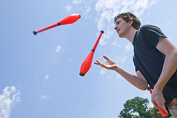 """Juggler throwing skittles into the air at the Nottingham University Student Union """"Sounds on the Downs"""" Green Fields Festival; part of Green Week 2008,"""