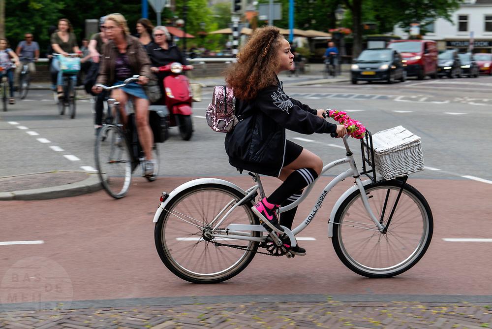Een meisje fietst met een fietskrat voorop door de binnenstad van Utrecht.<br /> <br /> A young girl is riding her bike at the city center of Utrecht.