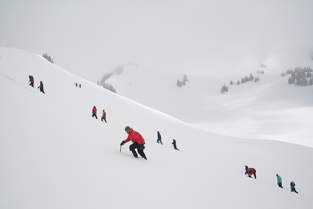 """University of Washington Climbing Club members ascend a snow slope during """"Snow School"""" at Paradise in Mount Rainier National Park, Washington. At the annual club event, members practice essential skills like glacier crevasse rescue and self arrest."""