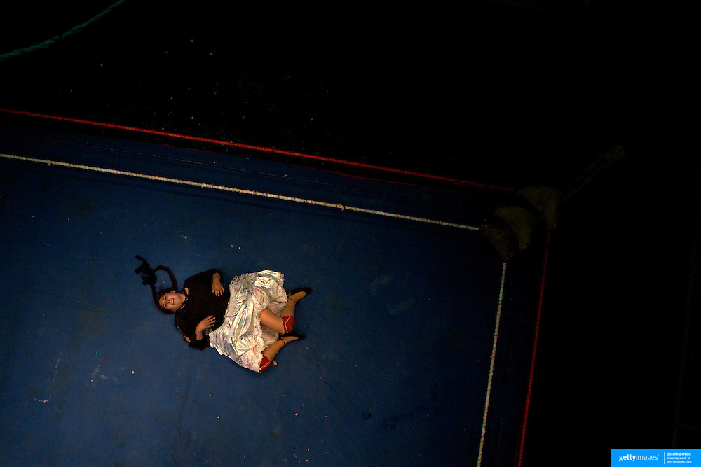 Cholita wrestler Martha La Altena lies prone on the canvas during her bout with Claudina the Condemned during the 'Titans of the Ring' wrestling group's Sunday performance at El Alto's Multifunctional Centre. Bolivia. The wrestling group includes the fighting Cholitas, a group of Indigenous Female Lucha Libra wrestlers who fight the men as well as each other for just a few dollars appearance money. El Alto, Bolivia, 14th March 2010. Photo Tim Clayton
