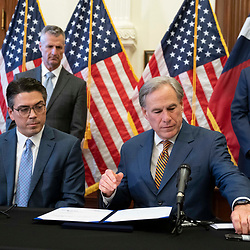 Texas Gov. Greg Abbott reaches for a pen to sign two bills strengthening the Texas power grid and infrastructure that were emergency items on his legislative agenda. The bills were in response to February's winter storm that nearly knocked out the Texas power grid.  At left is Rep. Chris Paddie, R-Marshall.