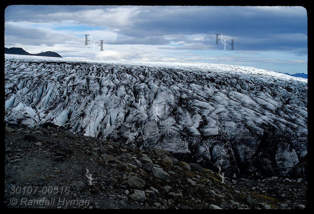 Black, silty foot of Skalafellsjokull glacier framed by ridge of rocky morraine; Iceland.