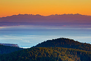 The Olympic Mountains are visible over the Salish Sea in the golden light of sunset in this view from the summit of Mount Erie in Anacortes, Washington.