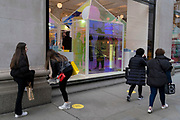 On the day that the UK government eased Covid restrictions to allow non-essential businesses such as shops, pubs, bars, gyms and hairdressers to re-open, young women shoppers pass a window of Selfridges, on 12th April 2021, in London, England.