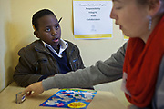 A young African boy looks at his volunteer reading teacher while she explains the rules of the game she is showing him.  The game is designed to improve children's literacy and is called 'Cloudy Sky' in Zonnebloem School, Cape Town, South Africa.  The volunteer has been provided to the school by Shine Centre which is a charity that aims to address the high illiteracy rate in South Africa by improving literacy levels among children in schools and disadvantaged communities.