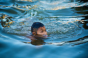13 JANUARY 2013 - BANGKOK, THAILAND:  A Thai boy swims in Khlong Bang Luang in Bangkok. The Bang Luang neighborhood lines Khlong (Canal) Bang Luang in the Thonburi section of Bangkok on the west side of Chao Phraya River. It was established in the late 18th Century by King Taksin the Great after the Burmese sacked the Siamese capital of Ayutthaya. The neighborhood, like most of Thonburi, is relatively undeveloped and still criss crossed by the canals which once made Bangkok famous. It's now a popular day trip from central Bangkok and offers a glimpse into what the city used to be like.     PHOTO BY JACK KURTZ