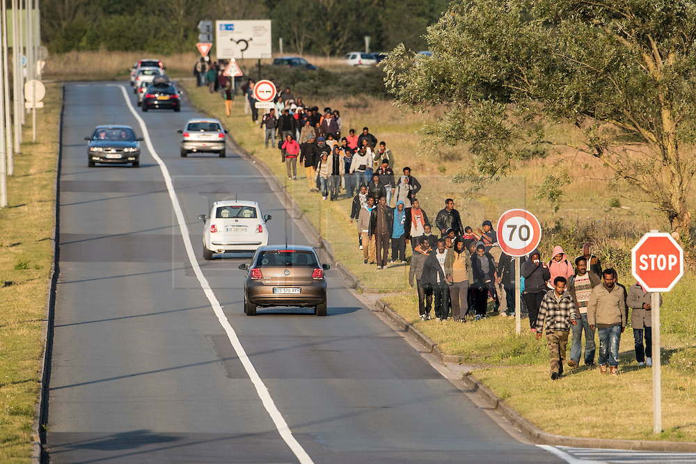 © London News Pictures. Calais, France. Migrants make the long walk form their living camp to the Eurotunnel complex in order to try to gain access. The same journey, which takes roughly an hour and a half to walk, is made each night. Migrants attempting to reach the UK via the Eurotunnel at Calais in France. The situation has reached crisis point, which French police over run by attempts to cross the border. Photo credit: Ben Cawthra /LNP