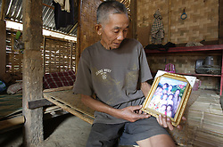 Thong,  65 years old.  He is a member of the HelpAge organised Older People's Groups in Ban Thad Teun.<br /> He lives in a simple but neat house and shows the portrait photograph of his son and family that they sent a few years ago.<br /> Ban Thad Teun, Pakseng District, Luang Prabang Province, Lao PDR
