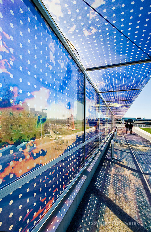 """View of """"Seattle Cloud Cover"""" glass bridge by artist Teresita Fernandez, Olympic Sculpture Park, Seattle Washington. The laminated glass bridge structure features an photographic interlayer depiction of clouds and vibrant colors."""