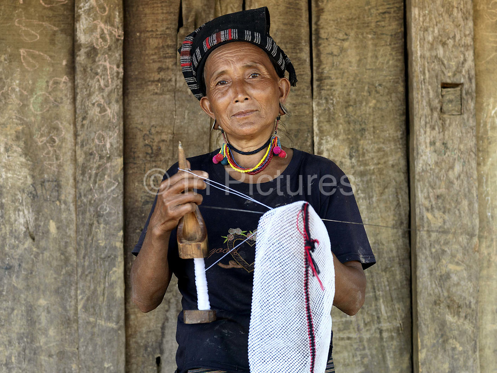 Wearing a traditional hat/headscarf made from handwoven cotton, a Mouchee woman stands outside her house in Ban Mouchee Nampok, Phongsaly province, Lao PDR, making a bag with a technique similar to crochet. One of the most ethnically diverse countries in Southeast Asia, Laos has 49 officially recognised ethnic groups although there are many more self-identified and sub groups. These groups are distinguished by their own customs, beliefs and rituals. Details down to the embroidery on a shirt, the colour of the trim and the type of skirt all help signify the wearer's ethnic and clan affiliations.