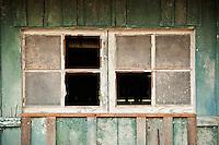 Broken windows of derelect horse barn, California