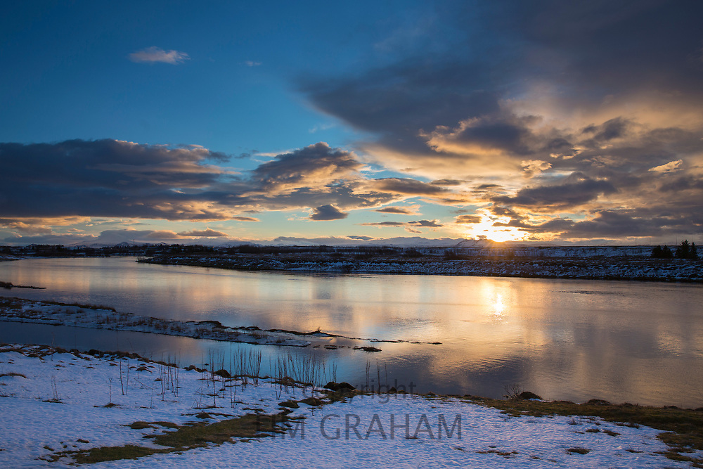 River Ranga with setting sun and puffy clouds over typical Icelandic landscape in Hella, South Iceland