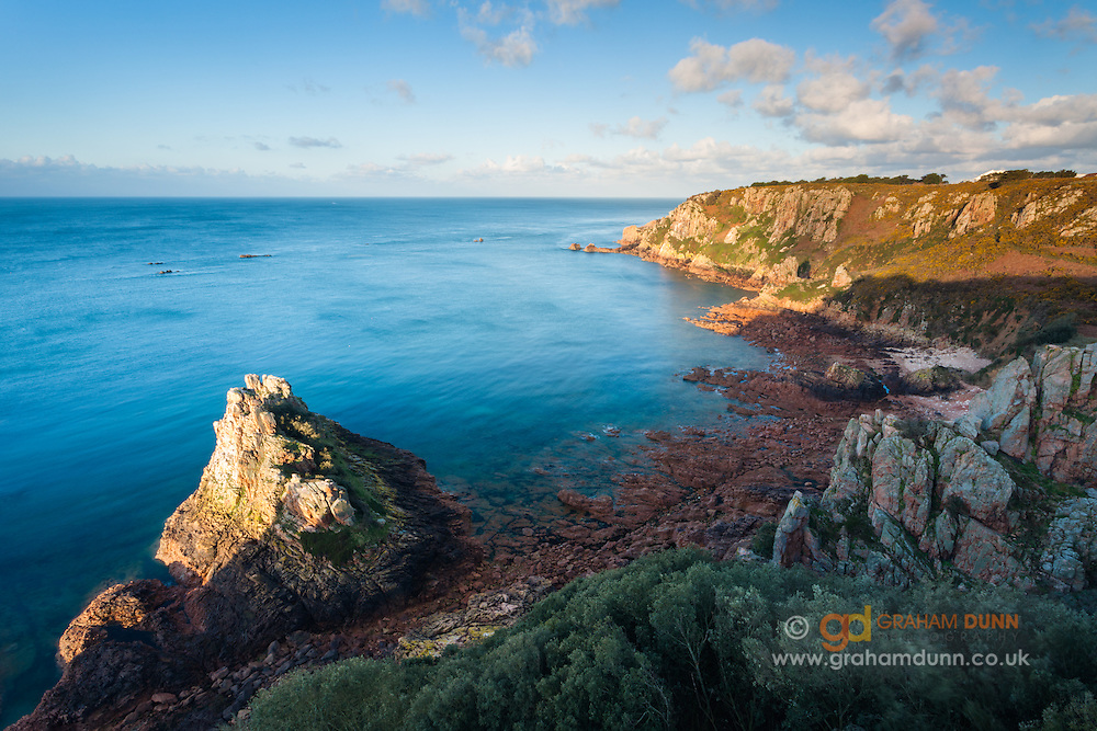 Dawn light catches the rocks of Fiquet Bay on the south coast of Jersey. Channel Islands.