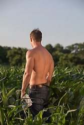 back of a muscular shirtless man walking in a field