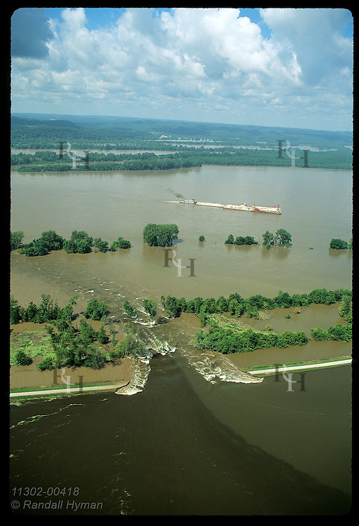 Flood surges thru manmade hole in levee back into Mississippi as barge w/rocks passes;Prair Rochr Illinois