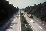 A 1960s aerial view from a bridge, of a German autobahn carrying VW Beetles, a Mercedes and trucks, in 1968, in North Rhine-Westfalia, Germany.