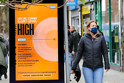 © Licensed to London News Pictures. 28/10/2020. London, UK. A woman wearing a face covering walks past a COVID-19 high alert level sign in north London. Pressure is mounting on the Prime Minister Boris Johnson and on ministers to impose a second national lockdown, amid reports that the SAGE (Scientific Advisory Group for Emergencies) calls for the second COVID-19 lockdown across the UK, as coronavirus cases are increasing. SAGE believes that the second wave could be deadlier then the first wave in the spring.  Photo credit: Dinendra Haria/LNP