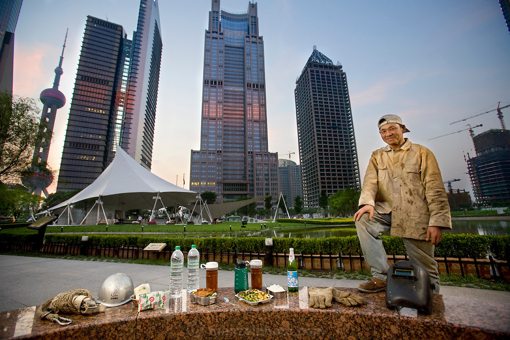 Construction welder Huang Neng, with his typical day's worth of food in Pudong's Lujiazui Central Green Park in Shanghai, China. (From the book What I Eat: Around the World in 80 Diets.) The caloric value of his day's worth of food on a typical day in June was 4300 kcals. He is 36 years of  age; 5 feet, 6 inches tall and 136 pounds. The migrant welder has worked on a dozen trophy skyscrapers on the Huangpu River in Pudong New Area, across the river from old Shanghai. His current project is the Zhongrong Jasper Tower, at far right, which will top out at 48 floors?a short-statured building compared to its neighbors. MODEL RELEASED.