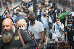 © Licensed to London News Pictures.  14/07/2021. London, UK. Members of the public arrive at King's Cross Station as face covering must be worn on London's transport despite easing Lockdown restriction on 19 July. Photo credit: Marcin Nowak/LNP