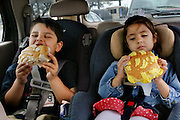 After going grocery shopping with their mother and grandmother, Brian and Brianna Fernandez devour Texas-size pan dulces in the back of the family minivan in San Antonio, Texas. (From the book What I Eat: Around the World in 80 Diets.)  MODEL RELEASED.