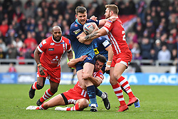 Wigan Warriors' Joe Greenwood is tackled by Salford Red Devils' Niall Evalds (left) and Salford Red Devils' Jansin Turgut (right) during the Betfred Super League match at the AJ Bell Stadium, Salford.
