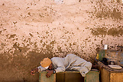 An elderly Egyptian sleeps in the mid-day shade of a mud-splattered wall in the village of Bairat on the West Bank of Luxor, Nile Valley, Egypt. Stretched out on an upturned wooden box, the old man dozes peacefully at a time during the day when people stay indoors and sleep in their homes or businesses until cooler air once again flows through villages and cities alike.