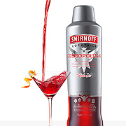 Smirnoff Cosmopolitan beauty packshot on white glossy background. Cocktail pouring into glass creating a splash with orange peel and zest Ray Massey is an established, award winning, UK professional  photographer, shooting creative advertising and editorial images from his stunning studio in a converted church in Camden Town, London NW1. Ray Massey specialises in drinks and liquids, still life and hands, product, gymnastics, special effects (sfx) and location photography. He is particularly known for dynamic high speed action shots of pours, bubbles, splashes and explosions in beers, champagnes, sodas, cocktails and beverages of all descriptions, as well as perfumes, paint, ink, water – even ice! Ray Massey works throughout the world with advertising agencies, designers, design groups, PR companies and directly with clients. He regularly manages the entire creative process, including post-production composition, manipulation and retouching, working with his team of retouchers to produce final images ready for publication.