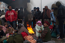 Licensed to London News Pictures. 24/10/2015. Spielfeld, Austria. Migrants warm themselve by a fire at a checkpoint as they wait for a bus in Spielfeld, Austria at a border crossing between Austria and Slovenia. Photo: Marko Vanovsek/LNP