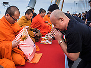05 DECEMBER 2016 - BANGKOK, THAILAND:  People pray after presenting alms to Buddhist monks during a merit making ceremony on Bhumibol Bridge. Tens of thousands of Thais gathered on Bhumibol Bridge in Bangkok Monday to mourn the death of Bhumibol Adulyadej, the Late King of Thailand. The King died on Oct 13 after a lengthy hospitalization. December 5 is his birthday and a national holiday in Thailand. The bridge is named after the late King, who authorized its construction. 999 Buddhist monks participated in a special merit making ceremony on the bridge.      PHOTO BY JACK KURTZ
