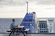 Kiel, Germany, 17/07/2013.<br /> Man yawning on Kiel to Klaipeda ferry at dusk.