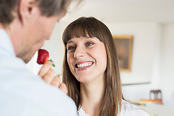 Mid adult woman feeding strawberry to mature man, smiling