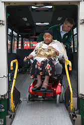 Driver using electronic lift ramp to help wheelchair user off the mini bus,